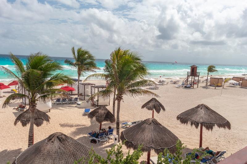 Caribbean beach with white sand, turquoise sea, palm trees, huts and cloudy sky stock photography