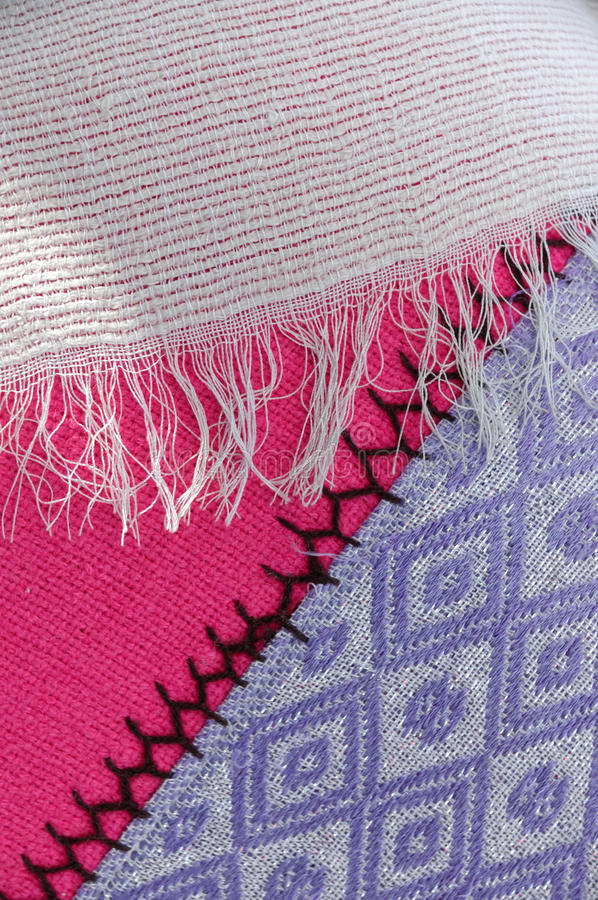 Detail of traditional Ethiopian woven cloth tibeb in different colors. Detail of three pieces of traditional Ethiopian woven cloth in different bright colors stock photo