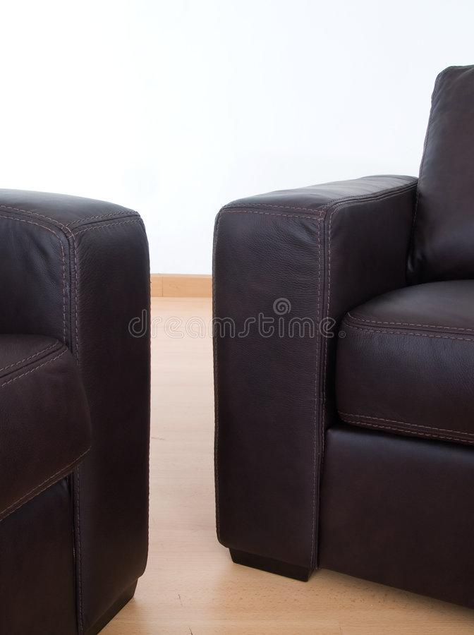 Detail of two brown leather sofas. Details of two brown leather sofas with visible seams on a parquet floor and with a white wall behind royalty free stock photography