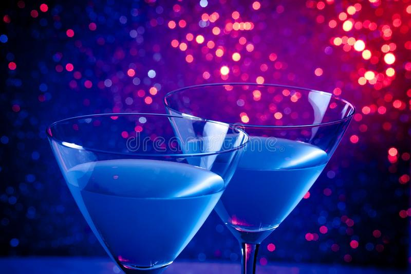 Detail of two glasses of blue cocktail on table. Detail of two glasses of blue cocktail on blue and violet tint light bokeh background on table stock photo