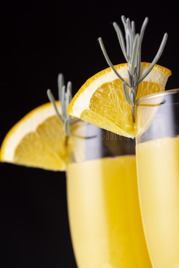 Detail of two mimosa cocktails. Detail of mimosa cocktails in champagne glasses with orange juice and sparkling wine decorated with lavender leaves and orange stock photography
