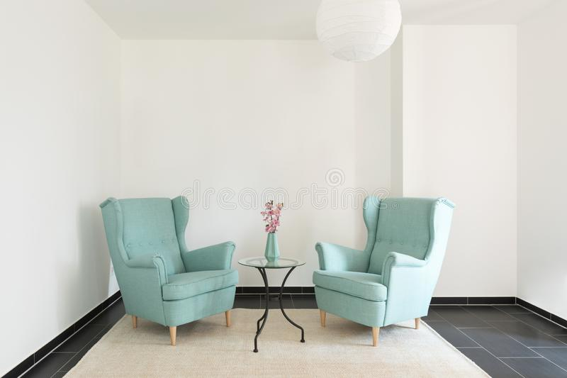 Detail of two turquoise armchairs in empty apartment stock photos