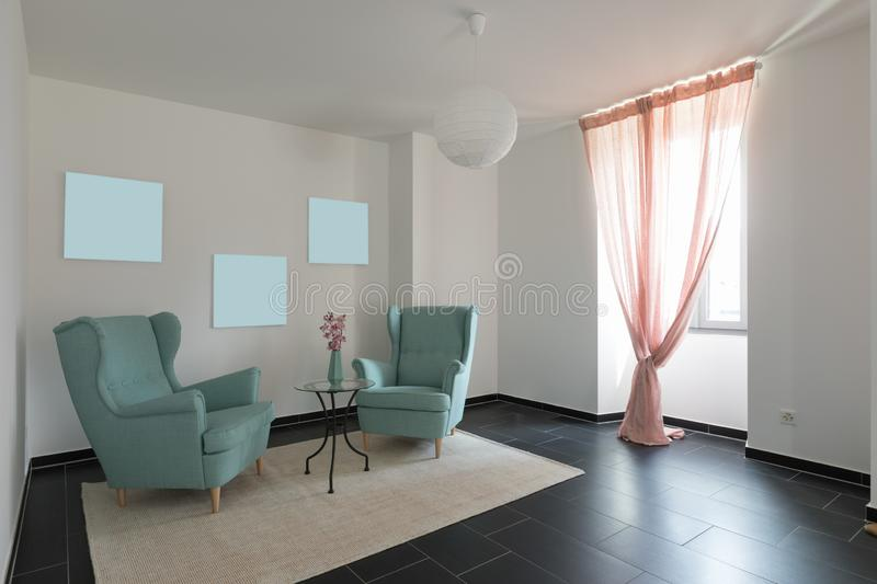 Detail of two turquoise armchairs in empty apartment royalty free stock photo