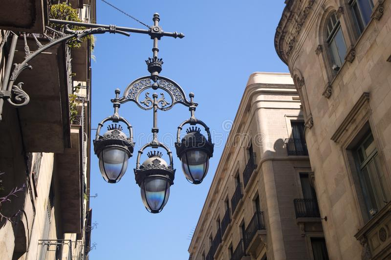 Detail of typical street lamp with facade of old buildings near. Sant James Sant Jaume Square in Barcelona, Spain, place where City Council of Barcelona and stock images
