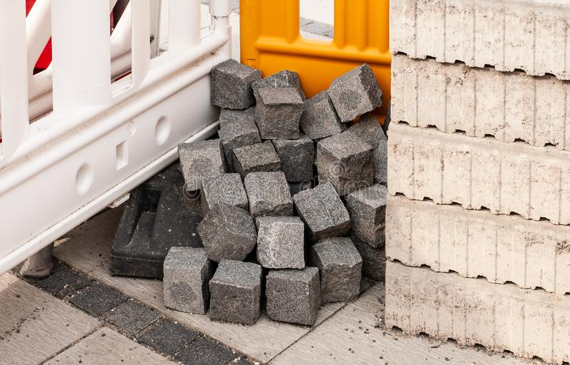 Small heap of granite sett stones at construction site. Detail of urban construction site with plastic barriers, sett stones and concrete blocks stock images
