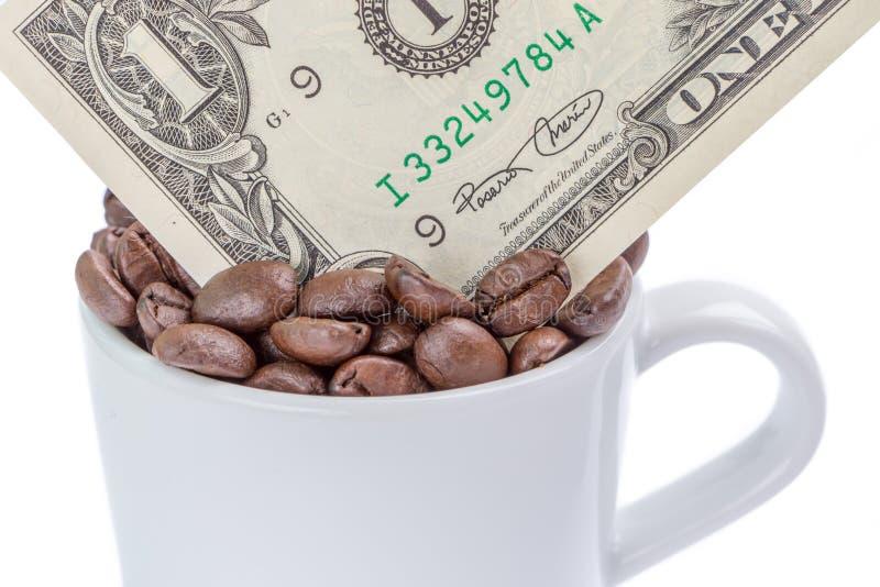 Detail van één Amerikaanse dollarbankbiljet in een kop koffiebonen op whi royalty-vrije stock afbeeldingen