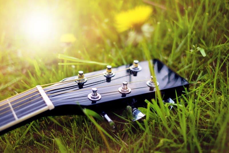 Detail van akoestische gitaar op een gras Natuurlijke achtergrond met bloemen, gras en zon Muzikaal instrument royalty-vrije stock fotografie