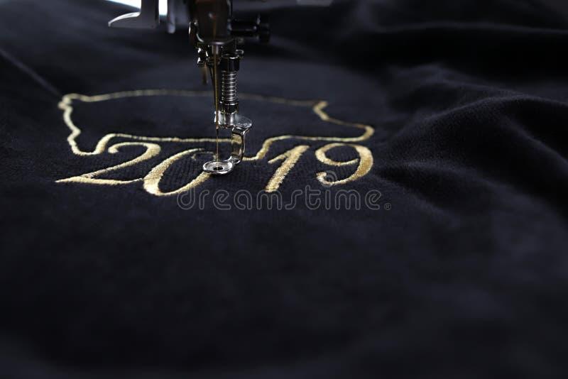 Detail van borduurwerkmachine die het Chinese nieuwe jaar van 2019 beweging veroorzakend met kostbaar gouden garen op zwart fluwe royalty-vrije stock afbeeldingen