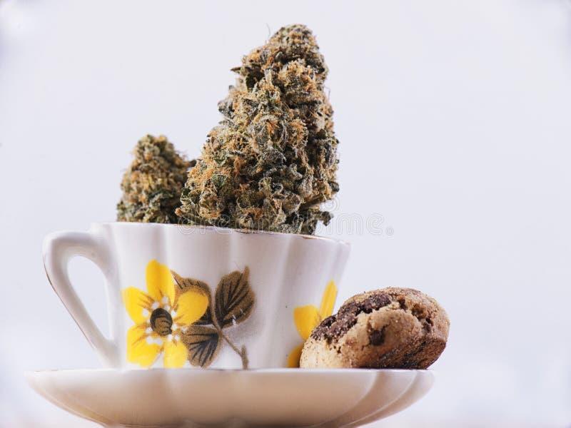 Detail van cannabis nug en koffiekop met chocoladeschilferkoekje royalty-vrije stock fotografie