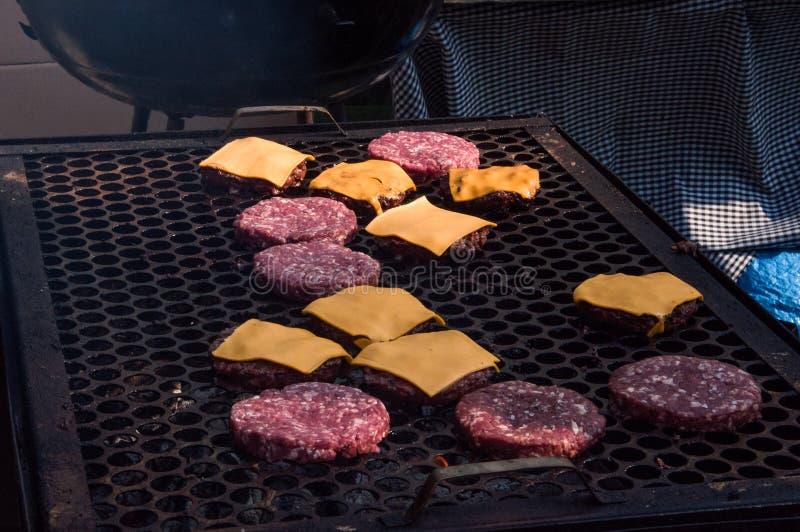 Detail van de draagbare messingsgrill van de chef-kok Roosterend burgers en cheeseburgers met het branden van steenkool BCoqueiro stock fotografie