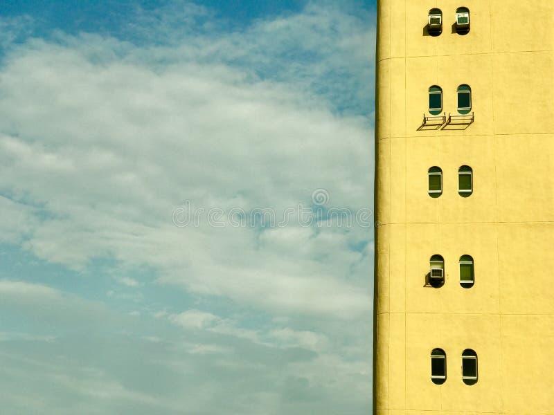 Detail van de gele bouw met ovale vensters en bewolkte blauwe hemel stock afbeelding