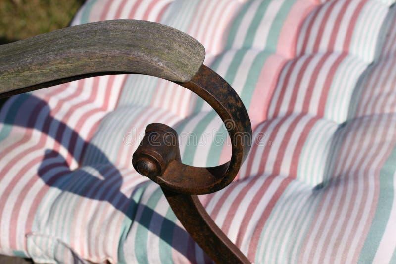 Detail van de roestige stoel van het metaalijzer met houten handvatten in tuin dichte omhooggaand met gestreept hoofdkussen in zo stock fotografie