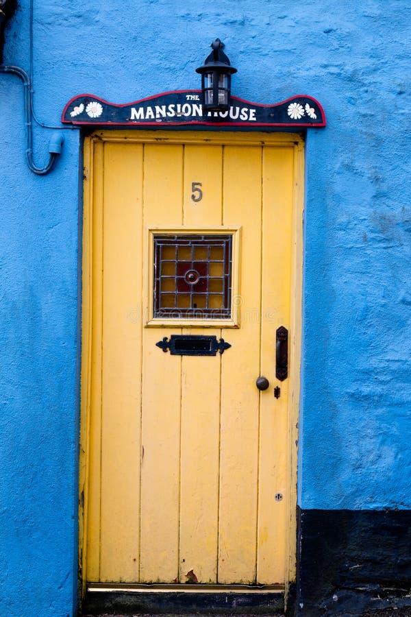 Detail van een gele deur van een blauw huis in het kustlijndorp van Kinsale royalty-vrije stock foto's