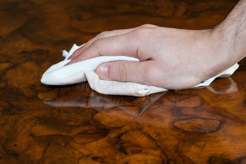 Detail van een hand die een houten meubilair schoonmaken royalty-vrije stock foto