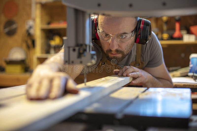 Detail van een timmerman aandachtig bij het snijden van een stuk van hout met precisie royalty-vrije stock fotografie