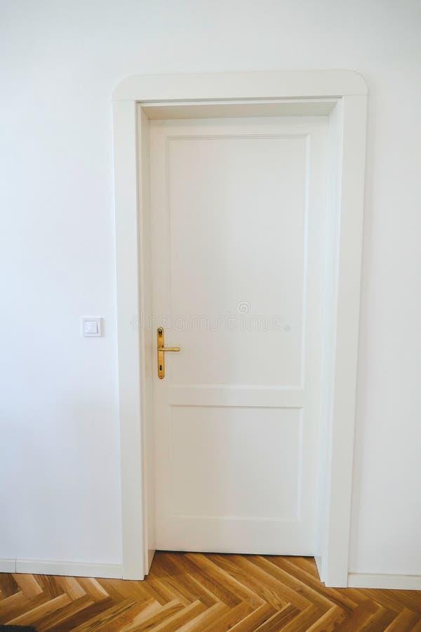 Detail van een witte deur met een houten vloer stock afbeelding
