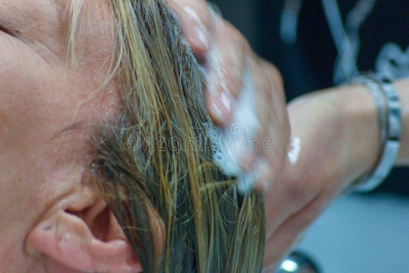 detail van een woman& x27; s gezicht terwijl zij bij hairdresser& x27 is; s die haar haar doen stock foto