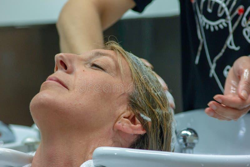 detail van een woman& x27; s gezicht terwijl zij bij hairdresser& x27 is; s die haar haar doen royalty-vrije stock afbeeldingen