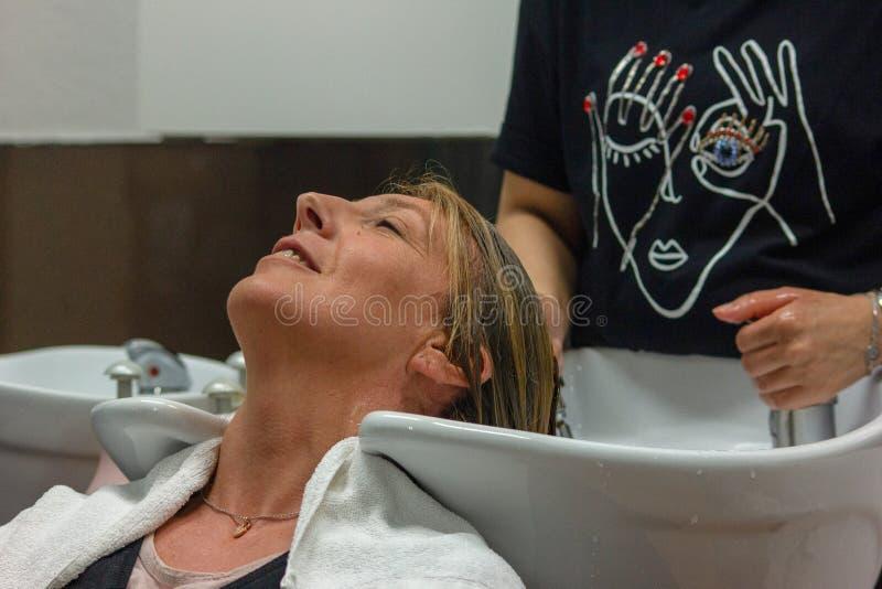 detail van een woman& x27; s gezicht terwijl zij bij hairdresser& x27 is; s die haar haar doen royalty-vrije stock foto's