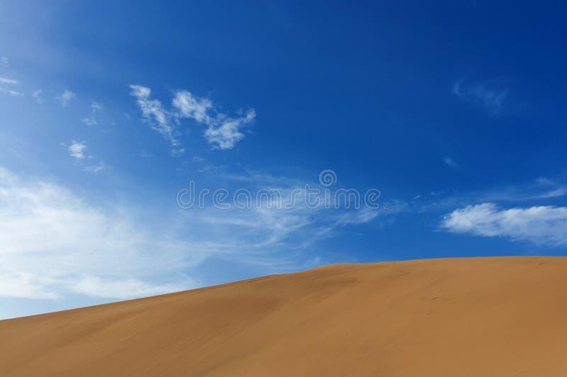 Detail van een zandduin tegen een blauwe hemel bij de het Weergalmen Zandberg dichtbij de stad van Dunhuang, in de Gansu-Provinci stock foto
