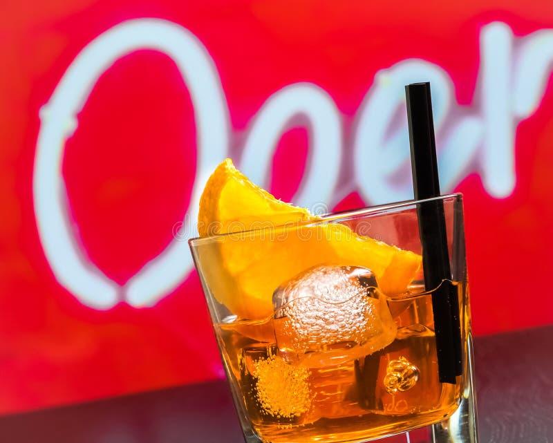 Detail van glas van aperolcocktail van het spritzaperitief met oranje plakken en ijsblokjes op barlijst, de achtergrond van de di stock afbeelding