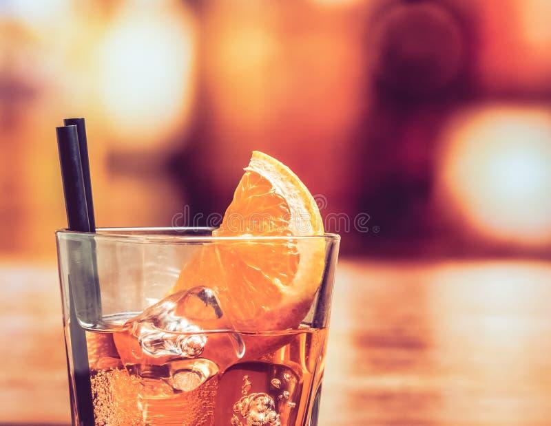 Detail van glas van aperolcocktail van het spritzaperitief met oranje plakken en ijsblokjes op barlijst, uitstekende atmosfeerach royalty-vrije stock afbeeldingen