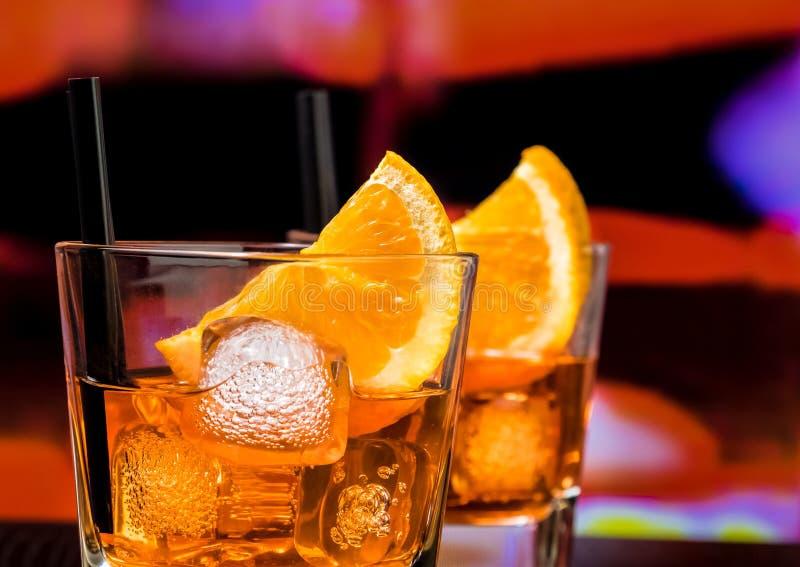 Detail van glazen van aperolcocktail van het spritzaperitief met oranje plakken en ijsblokjes op barlijst, uitstekende atmosfeera stock fotografie