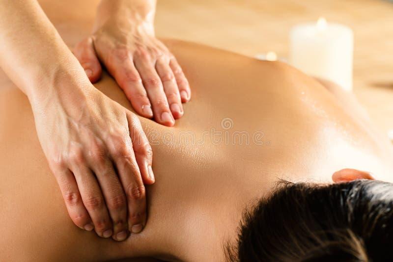 Detail van handen die vrouwelijke rug masseren stock foto
