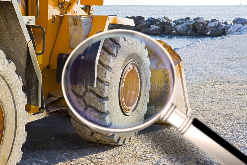 Detail van het wiel van het graafwerktuig bij de kust - Conceptenbeeld door een vergrootglas wordt gezien dat stock afbeeldingen