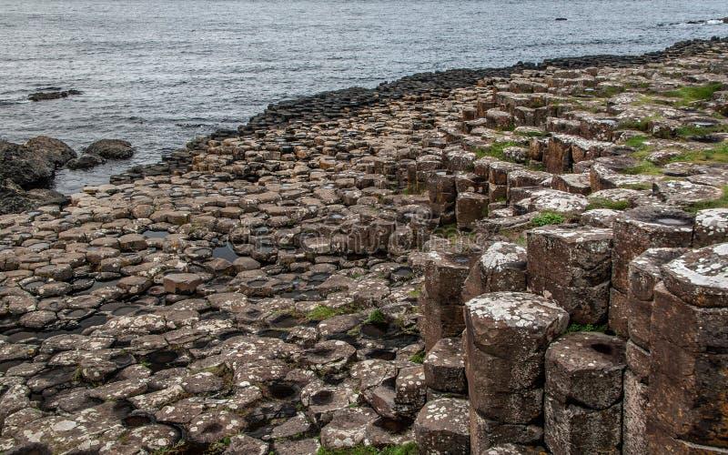 Detail van hexagonale steenpijlers bij Reuzenverhoogde weg, Noord-Ierland, overzees op achtergrond royalty-vrije stock afbeeldingen