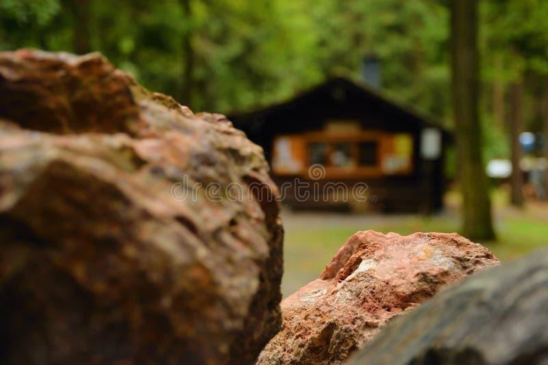 Detail van ijzerertssteen met houten plattelandshuisje op achtergrond in bos van Pressnitz-riviervallei dichtbij Steinbach-dorp i stock afbeelding