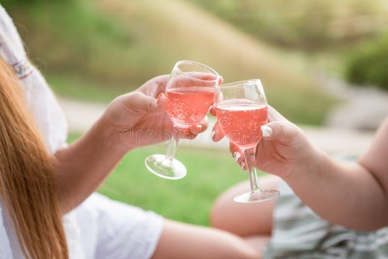 Detail van koppen die met roze wijn op in openlucht bij het park roosteren stock foto's