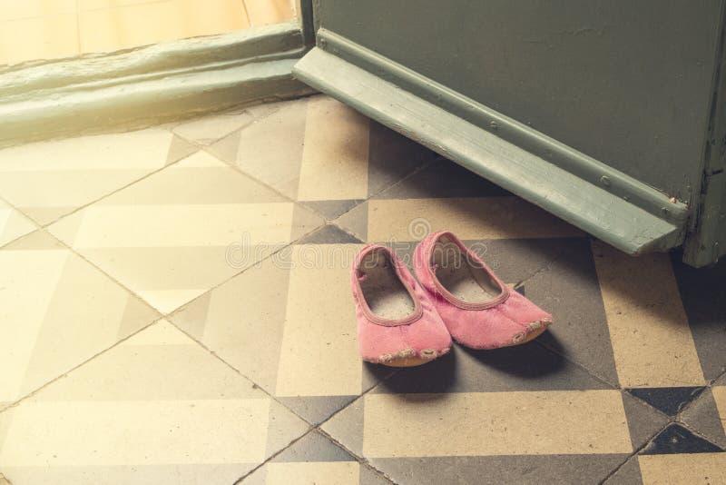Detail van oude en beschadigde kind` s roze dansende pantoffels of schoenen stock afbeelding