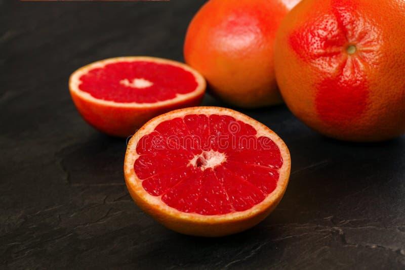 Detail van rode die grapefruit één citrusvrucht, op zwarte lei zoals raad wordt gehalveerd stock fotografie