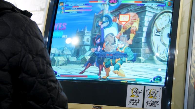 Detail van spelershanden die en met bedieningshendels en knopen op een oud arcadespel in wisselwerking staan spelen in een gokken stock afbeeldingen