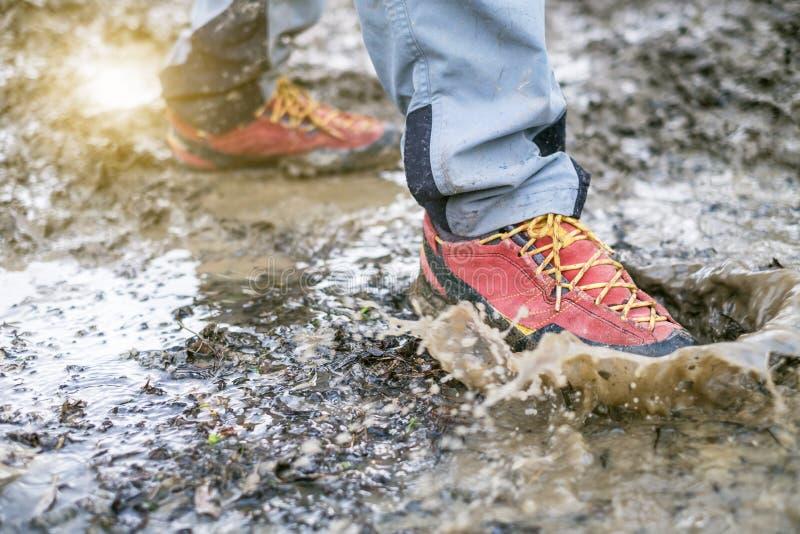 Detail van trekkingslaarzen in een modder Modderige wandelingslaarzen en plons van water Mens het bespatten in modderig en water  royalty-vrije stock fotografie