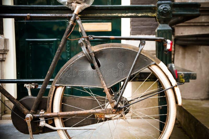 Detail van uitstekende oude roestige die fiets voor Nederlands huis wordt geparkeerd stock fotografie