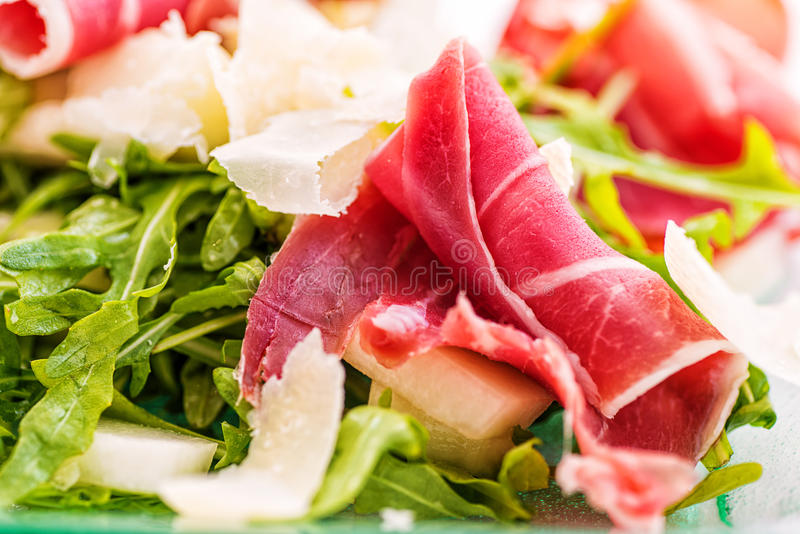 Detail van verse arugula plantaardige salade met ham en kaas op glasplaat op witte achtergrond, productfotografie voor r stock afbeelding