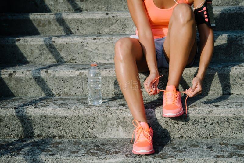 Detail van vrouw die loopschoenen rijgen alvorens op te leiden stock afbeeldingen