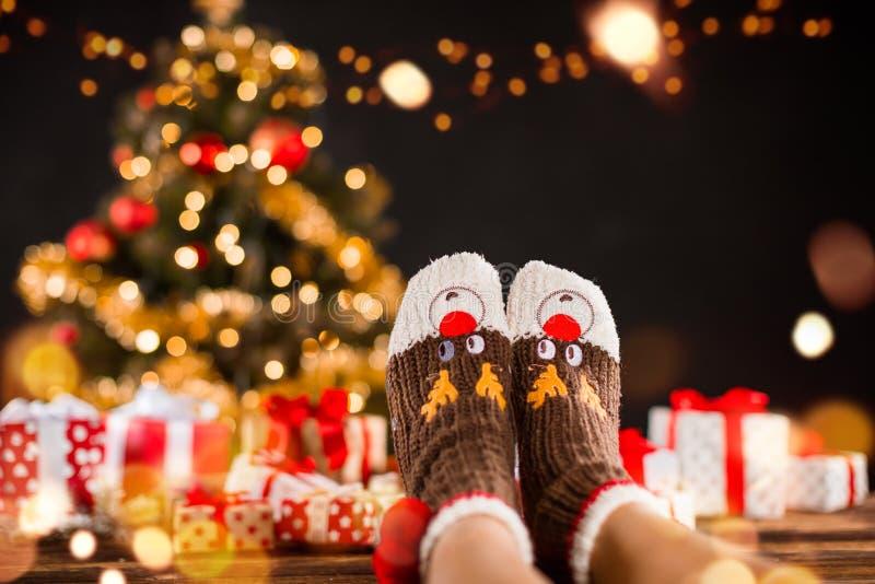 Detail van vrouwenbenen met gebreide sokken, Kerstboom met GIF stock foto