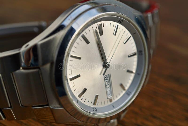 Detail van zilveren horloge met witte wijzerplaat op de houten achtergrond als symbool van tijd of juistheid stock afbeeldingen