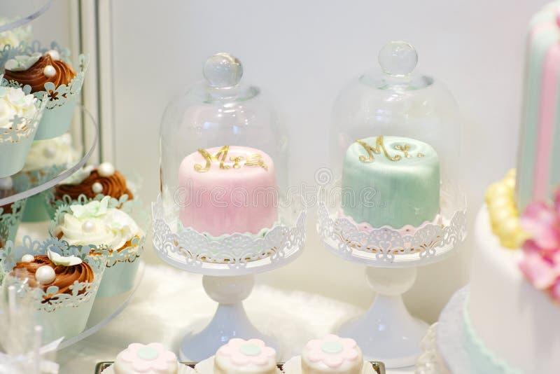 Detail van zoete lijst aangaande huwelijk met cupcakes en bruid en gro royalty-vrije stock foto's