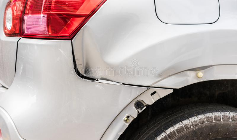 Car accident, close-up of damaged silver fender after crash royalty free stock image