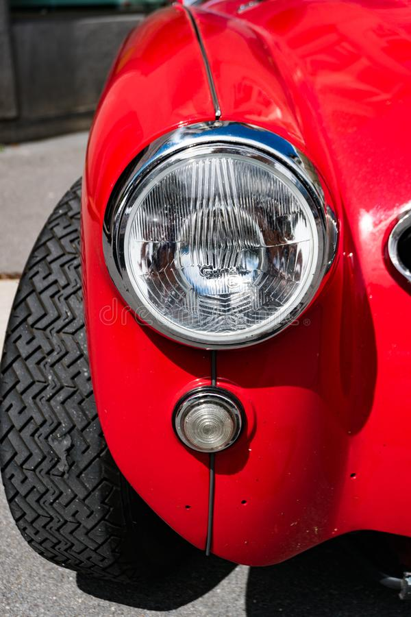 Detail view of the front fender and headlight of a classic red Austin-Healey sports car stock images