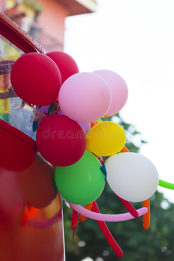 Detail view on various balloons outside. Low angle view on detail view of various balloons attached to back of red vehicle outside royalty free stock photos