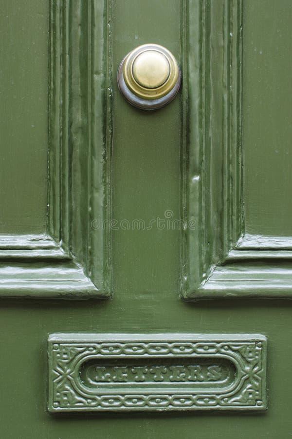 Detail of vintage green wooden door with brass doorknob knocker stock image