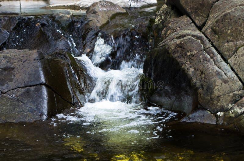 Detail von Felsen im Wasser in schwarzer Flussschlucht stockbilder