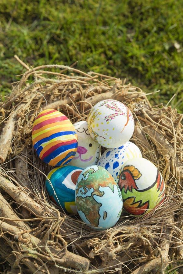 Detail von gemalten Ostereiern mit den verschiedenen Formen, Karikaturen und hellen Farben draußen gelegt in ein Vogelnest an ein stockfotografie
