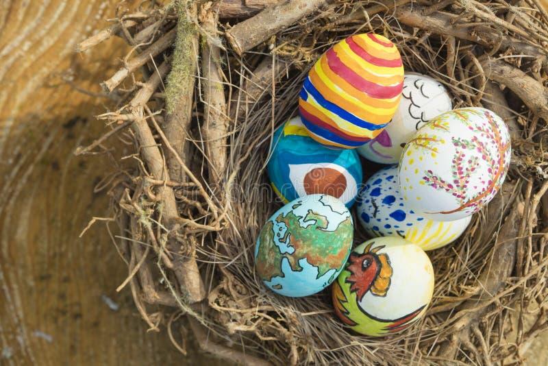 Detail von gemalten Ostereiern mit den verschiedenen Formen, Karikaturen und hellen Farben draußen gelegt in ein Vogelnest an ein stockfotos