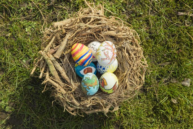 Detail von gemalten Ostereiern mit den verschiedenen Formen, Karikaturen und hellen Farben drau?en gelegt in ein Vogelnest an ein lizenzfreie stockfotografie